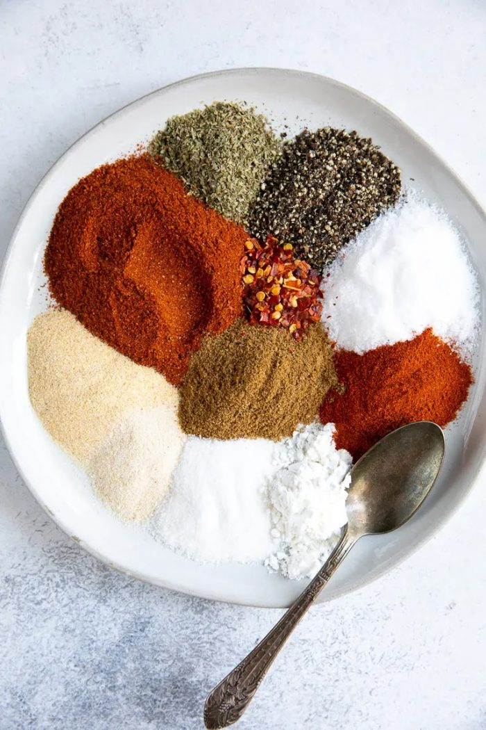 White plate filled with eleven difference spices and seasonings.