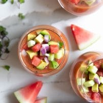 Overhead image of three glasses filled with watermelon gazpacho and topped with chopped avocado, cucumber, and red onion.