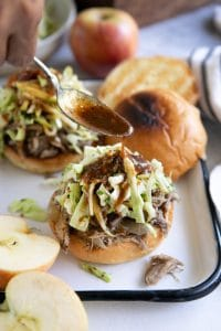 Spoon drizzling reduced apple cider sauce over the top of a toasted bun topped with shredded apple cider pulled pork and homemade apple coleslaw.
