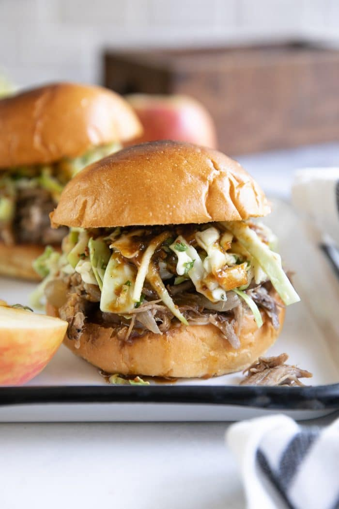 Apple cider pulled pork sandwiches topped with apple cabbage coleslaw.