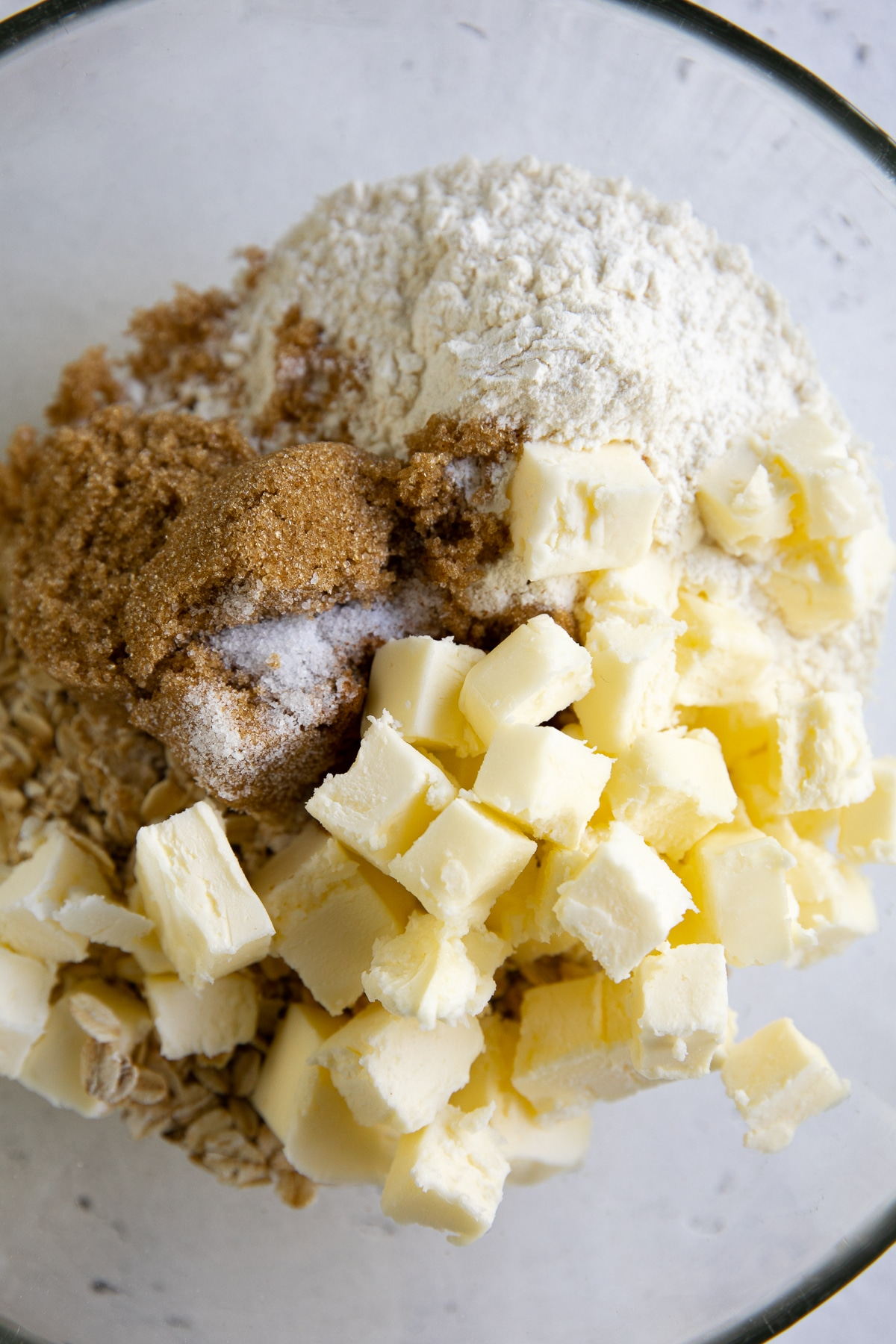 Mixing bowl filled with flour, brown sugar, rolled oats, cubed butter, and spices.