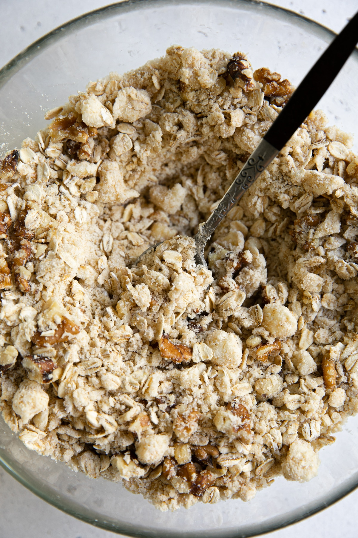 Flour, brown sugar, rolled oats, cubed butter, and spices mixed together with walnuts in a glass baking dish.