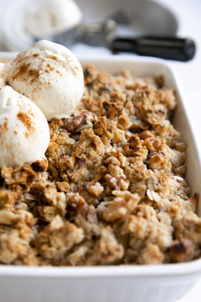 Baked apple crisp topped with three scoops of vanilla ice cream.