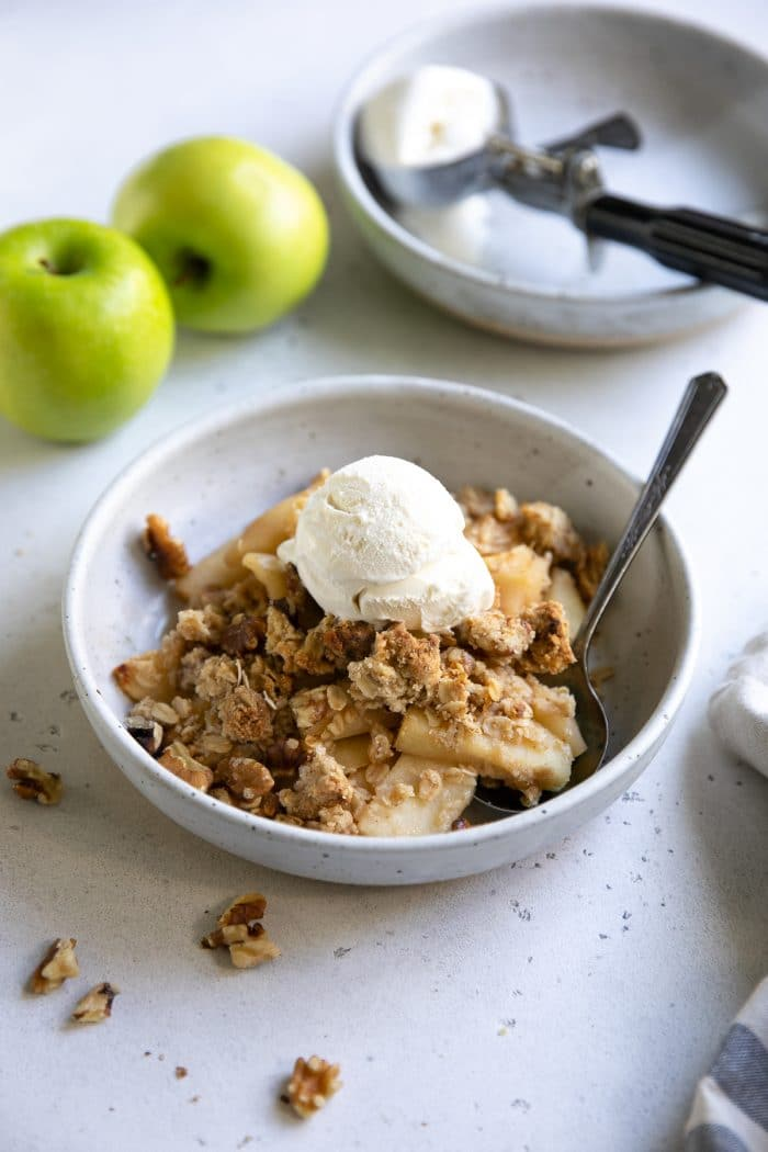 White bowl filled with apple crisp and topped with a scoop of vanilla ice cream.