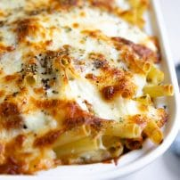 Cheesy bubbly baked ziti in a white casserole dish.