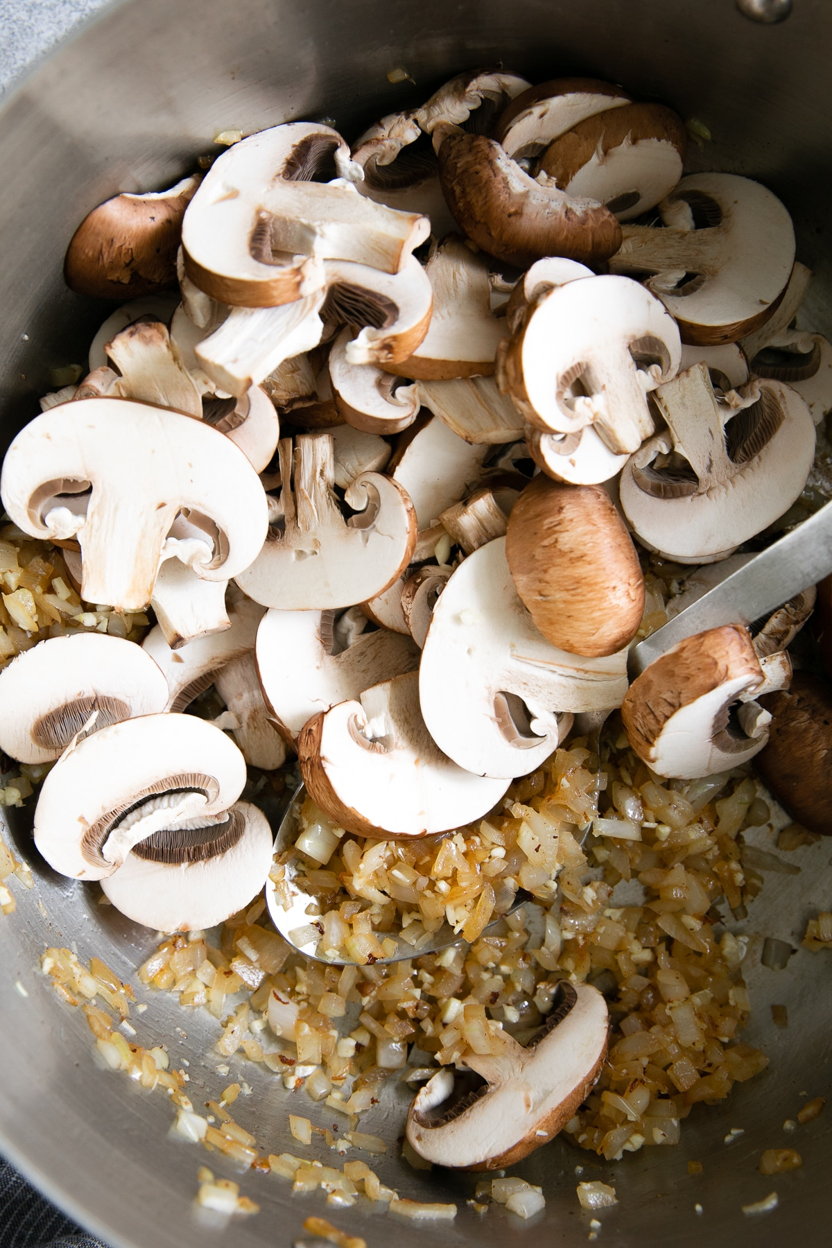 Onions, garlic, and mushrooms cooking in a large skillet.