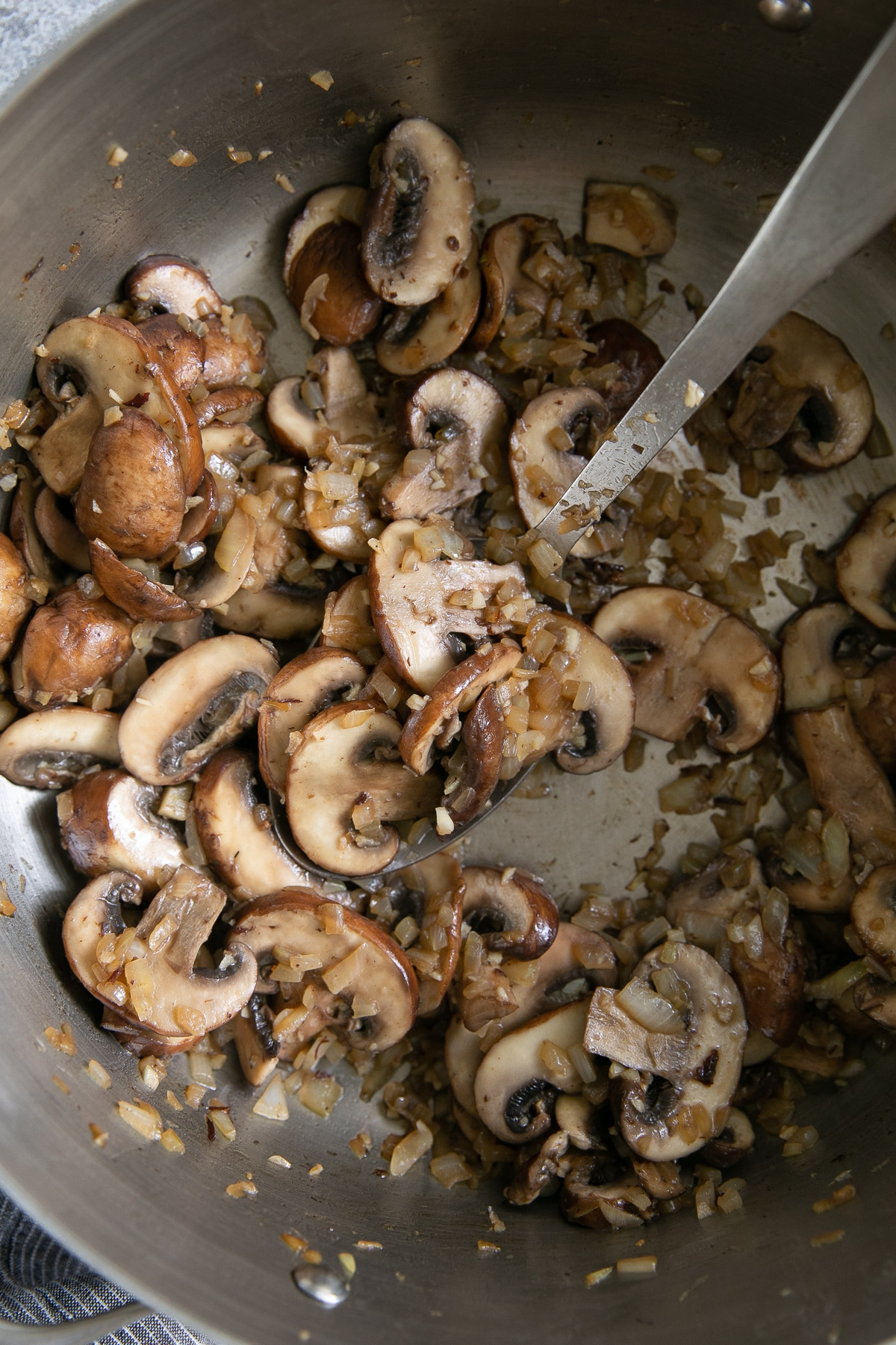 Large skillet filled with cooked onions, garlic, and mushrooms.