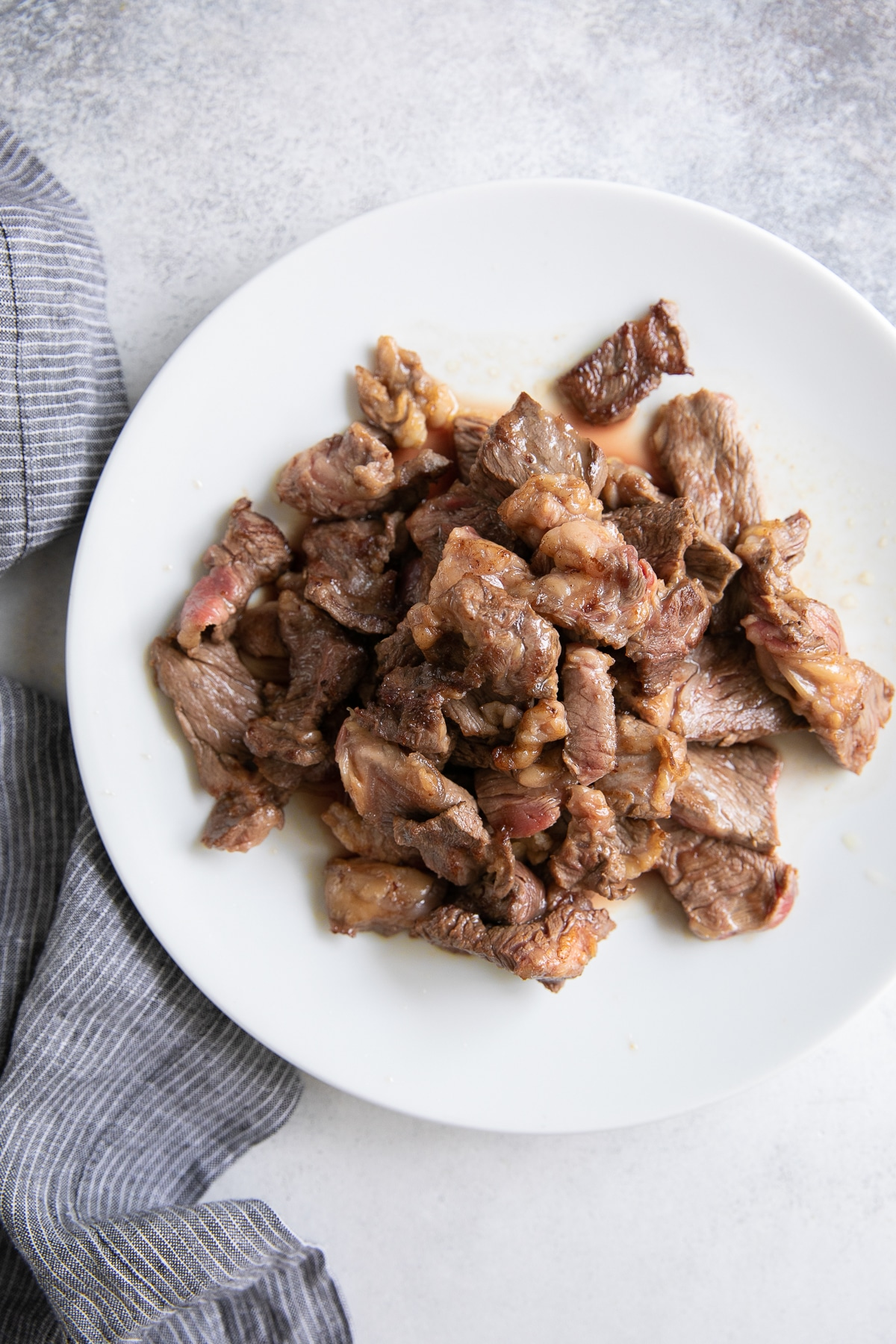 Thinly sliced pieces of cooked beef on a white plate.
