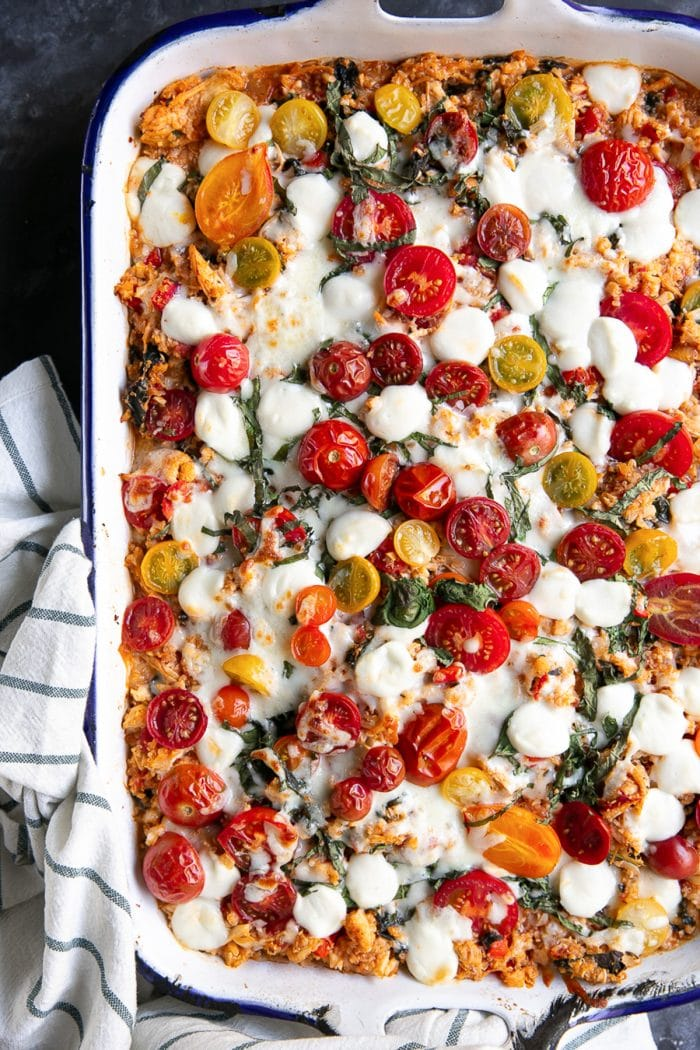 Overhead image of baked caprese casserole topped with cherry tomatoes and mozzarella pearls in a large white baking pan.