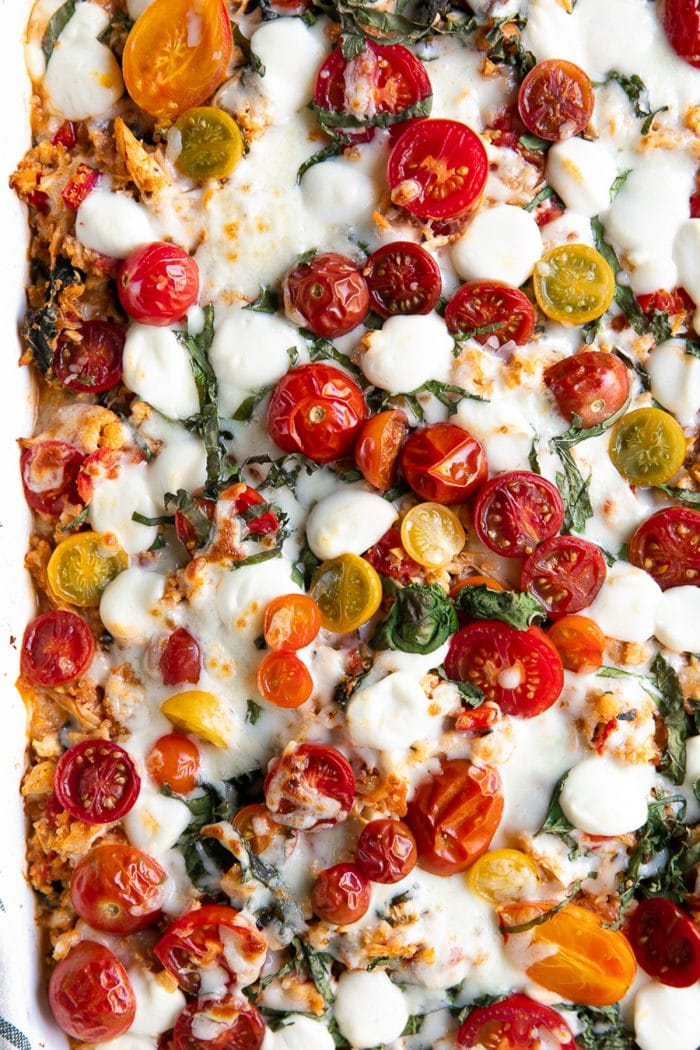 Overhead image of baked caprese casserole topped with cherry tomatoes and mozzarella pearls.