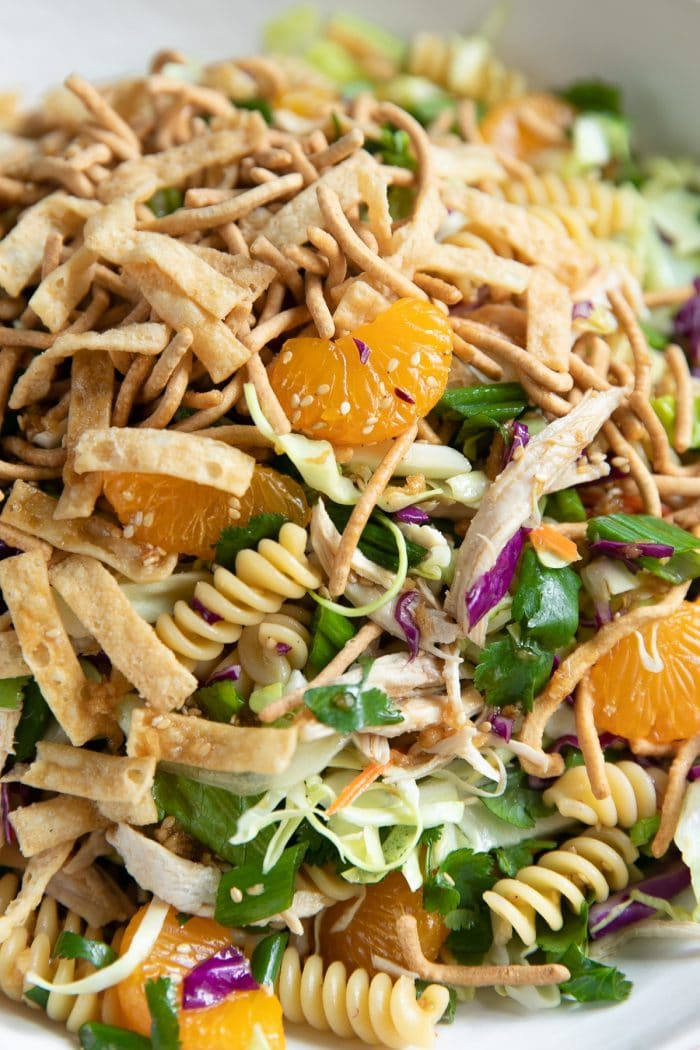 Asian Pasta Salad filled with cooked rotini noodles, red and green cabbage, green onions, fried wontons, shredded chicken, mandarin oranges, and carrots.