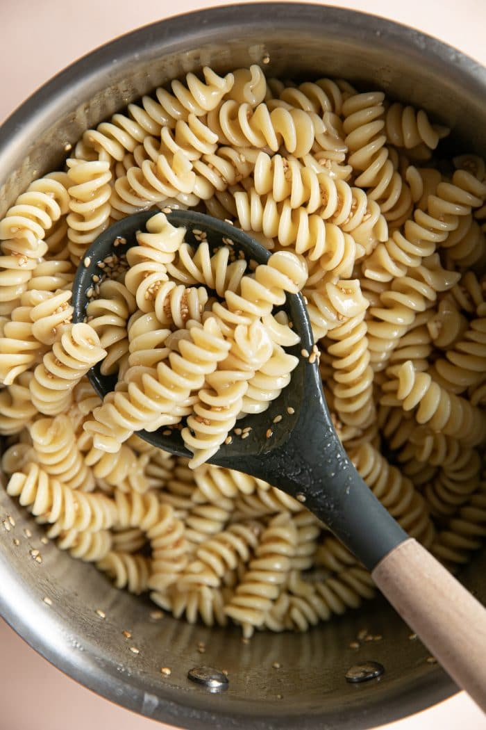 Sauce pot filled with cooked rotini pasta tossed in homemade sesame dressing.
