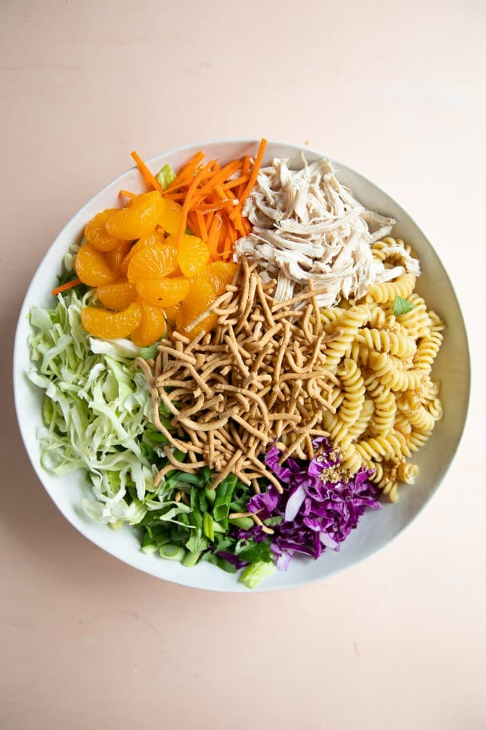 Large salad bowl filled with cooked rotini noodles, red and green cabbage, green onions, fried wontons, shredded chicken, mandarin oranges, and carrots.
