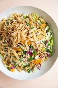 Large salad bowl filled with tossed together Asian pasta salad.
