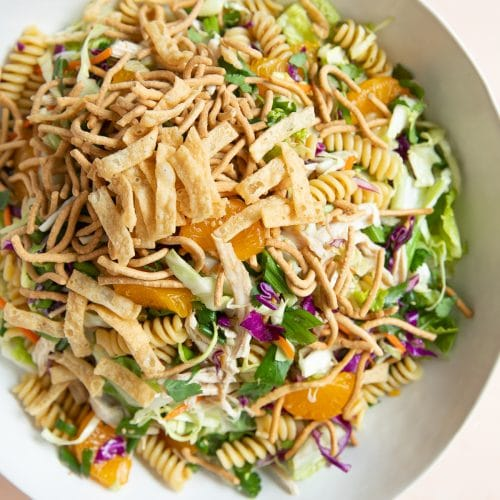 Large salad bowl filled with tossed together Asian pasta salad.