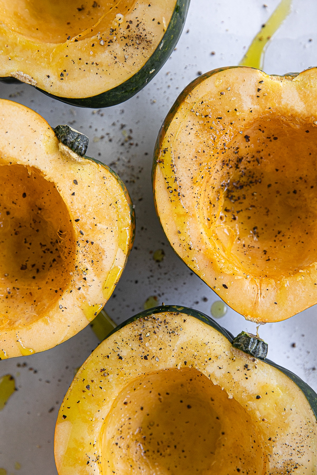 Raw halves of acorn squash on a baking sheet drizzled with olive oil and sprinkled with salt and pepper.
