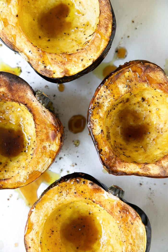 Four roasted acorn squash halves.
