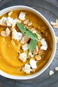 Bowl of acorn squash soup garnished with crackers, sesame seeds and fresh sage.