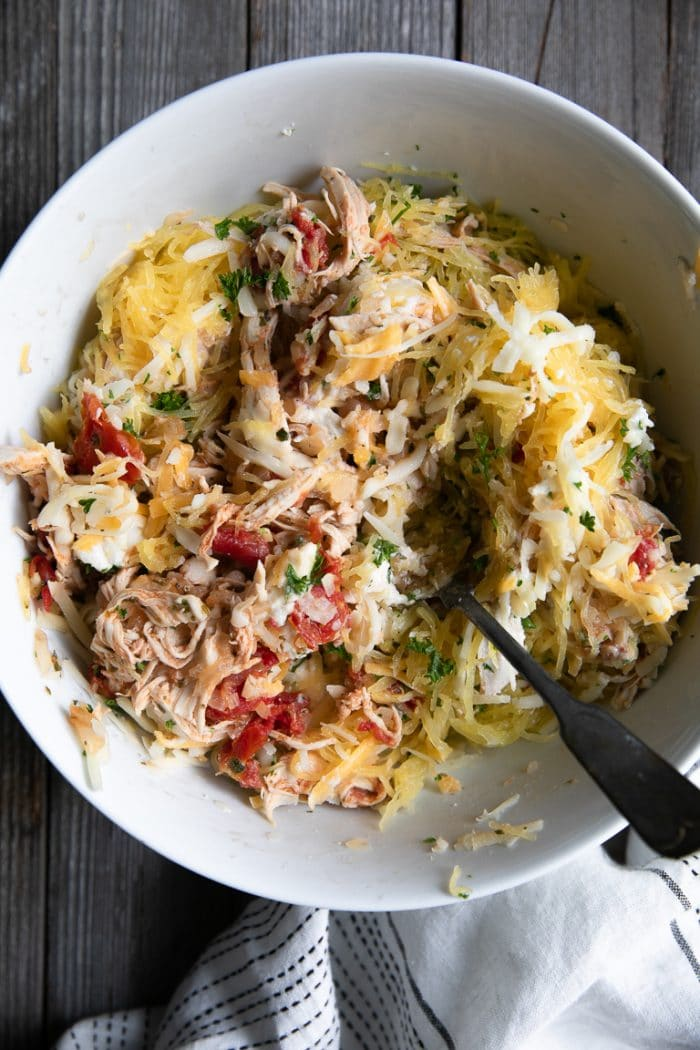 Large white bowl filled with mixed together shredded chicken and tomatoes, mixed shredded cheese, cooked spaghetti squash, chopped parsley, and ricotta cheese.