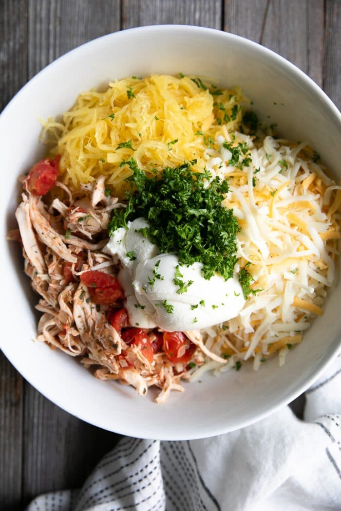 Large white bowl filled with shredded chicken and tomatoes, mixed shredded cheese, cooked spaghetti squash, chopped parsley, and ricotta cheese.