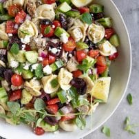 Overhead image of a large white serving bowl filled with Tortellini salad garnished with fresh oregano.