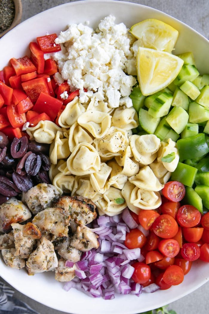 Large mixing bowl filled with cherry tomatoes, red onion, grilled greek chicken, kalamata olives, feta cheese, cucumber, green bell pepper, and cooked tortellini.