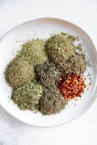 Piles of different dried herbs on a white serving plate.