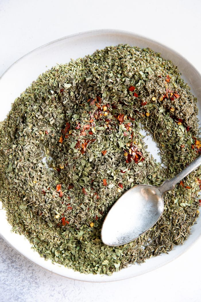 Mixed together dried herbs for on a white plate for Italian seasoning.