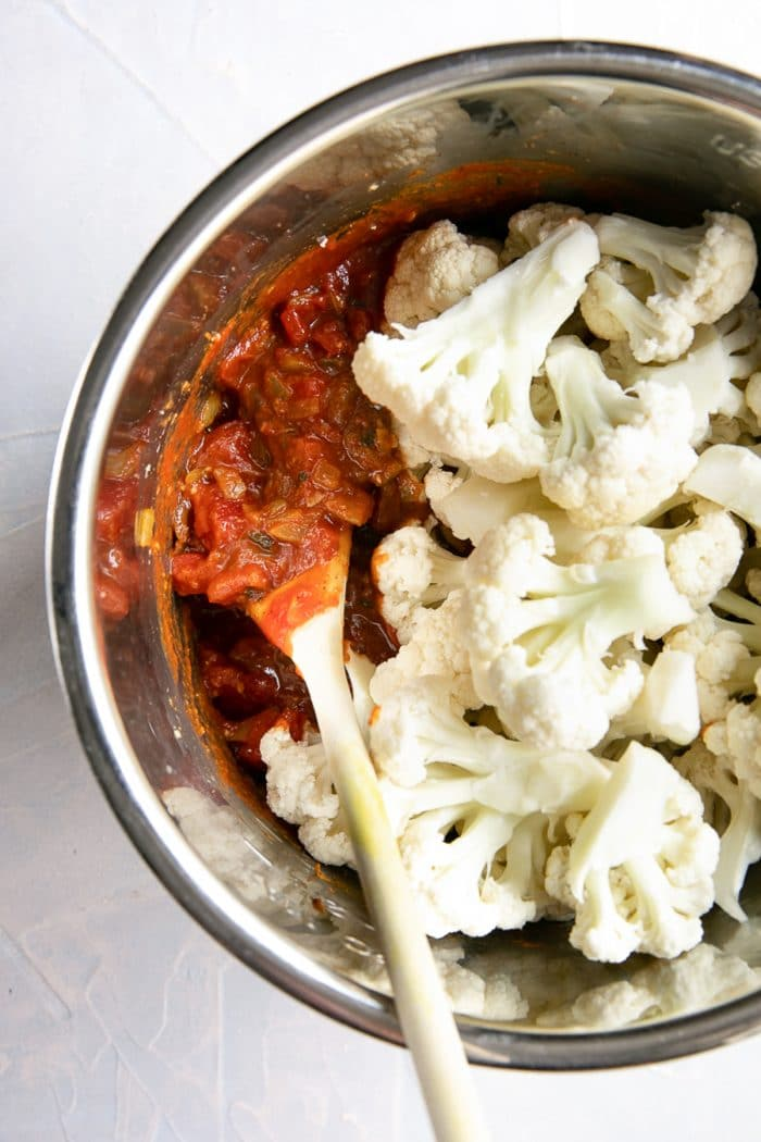 Instant pot bowl filled with sauteed onions, spices, and tomatoes with raw cauliflower florets.