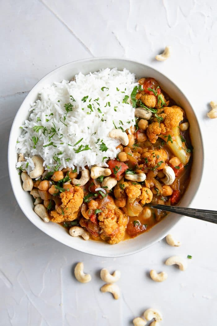 White bowl filled with vegetarian cauliflower and chickpea tikka masala with white rice.