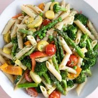 Large white pasta bowl filled with penne pasta and mixed spring vegetables such as asparagus, bell peppers, zucchini, tomatoes, and sprinkled with parmesan.