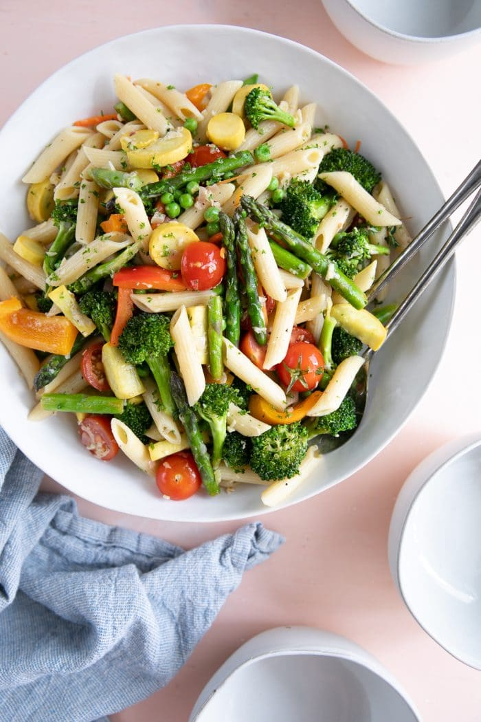 Large pasta bowl filled with pasta primavera.