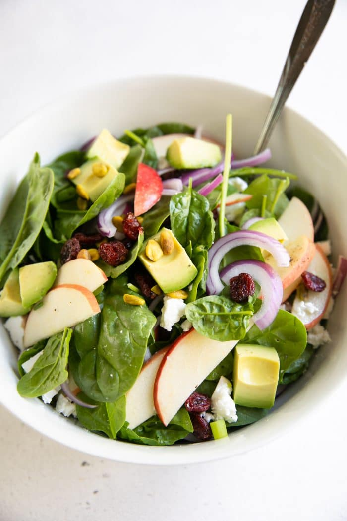 Salad bowl filled with baby spinach, sliced apples, avocado, sliced red onion, dried cranberries, pistachios, and feta cheese all tossed with a light red wine vinaigrette.