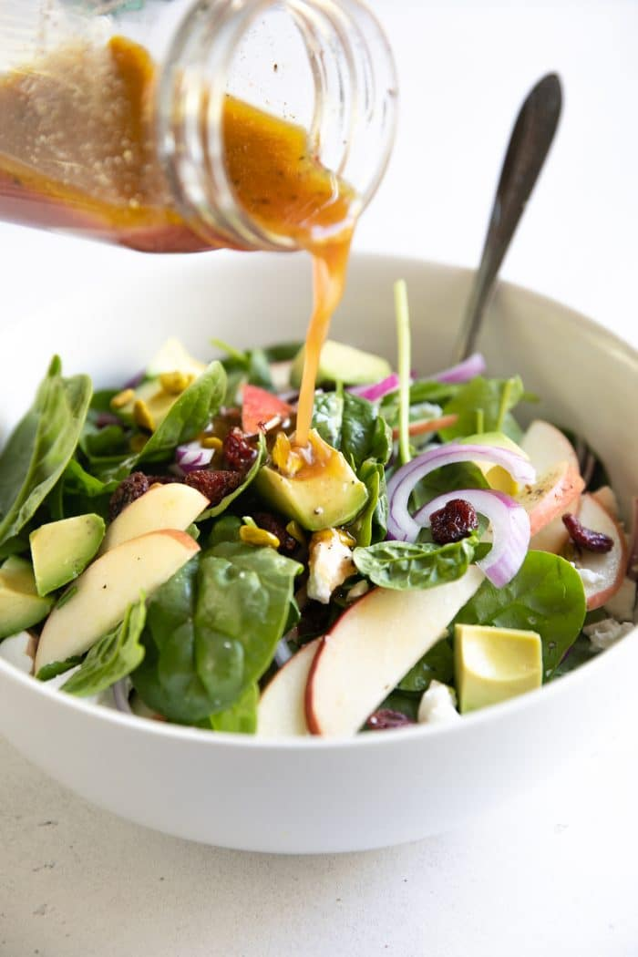 Red wine vinaigrette being poured onto a salad bowl filled with baby spinach, sliced apples, red onion, feta cheese, avocage, and pistachios.