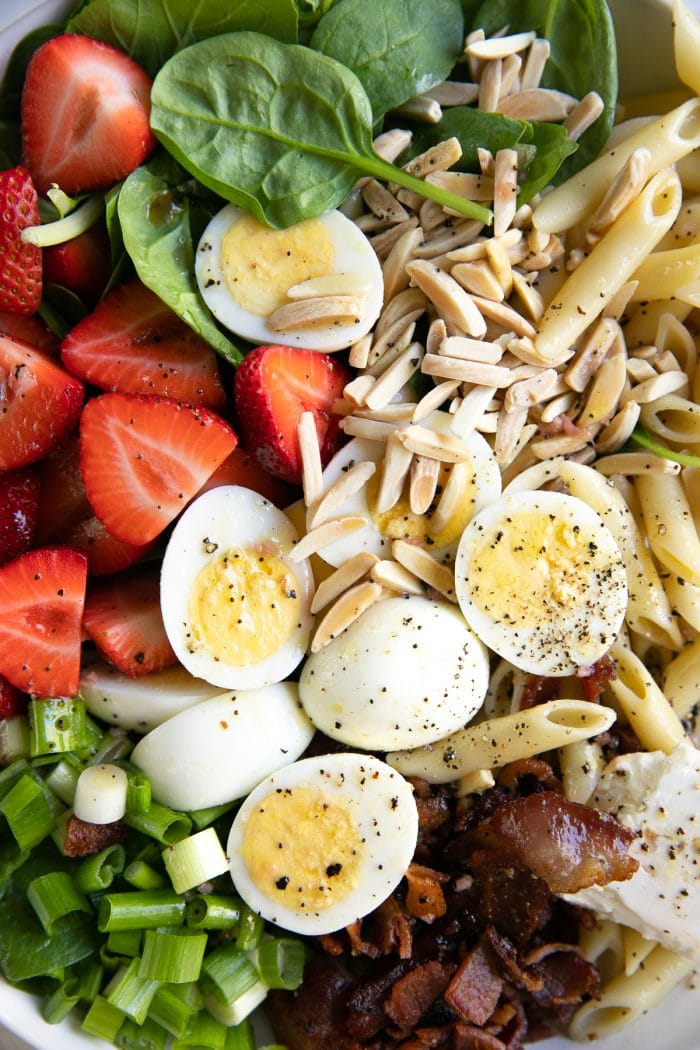 Large white salad bowl filled with penne, fresh spinach, feta cheese, strawberries, hard boiled eggs, and bacon.