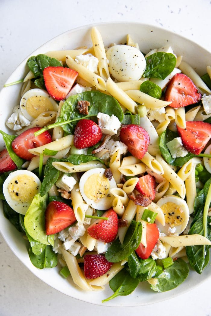 Large salad bowl filled with tossed together spinach pasta salad with strawberries, bacon, and hard-boiled eggs.