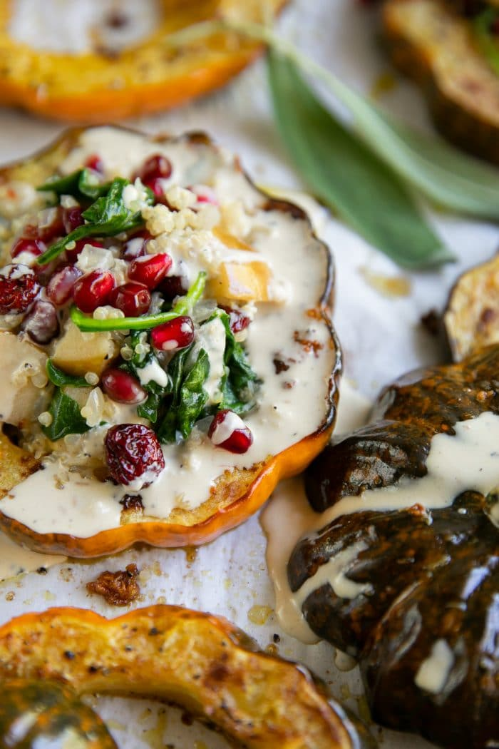 Roasted acorn squash rings topped with a quinoa, apple, spinach, and dried cranberry stuffing, topped with pomegranates, and drizzled with tahini dressing.