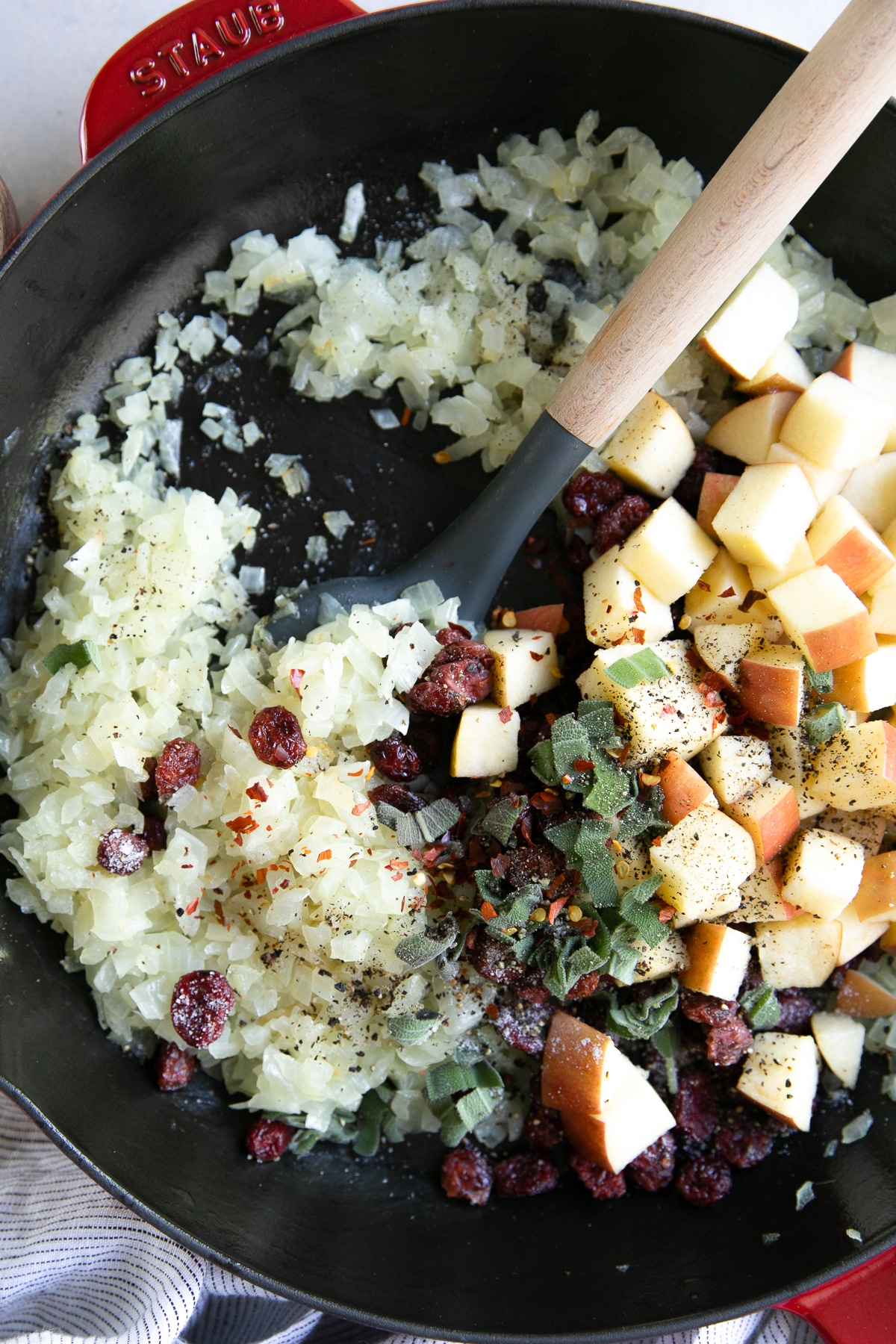 Skillet filled with sauteed onions, apples, sage, and dried cranberries.
