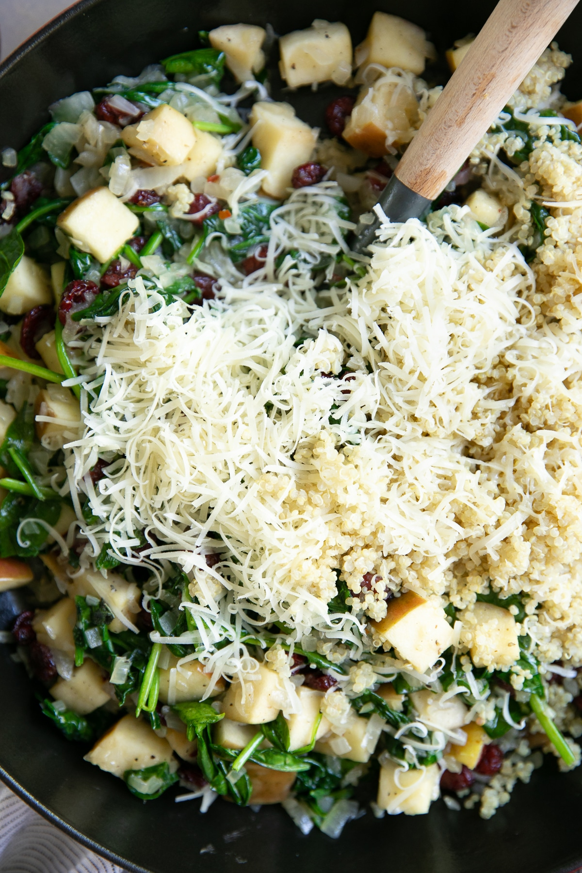 Skillet filled with cooked onions, apples, fresh sage, dried cranberries, spinach, and topped with cooked quinoa and shredded parmesan.