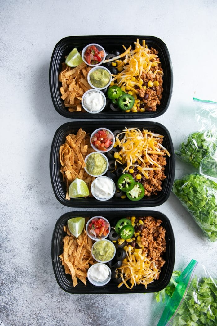 Three meal prep containers filled with seasoned ground turkey, cheese, olives, tortilla chips, and individual containers filled with sour cream, guacamole, and salsa.