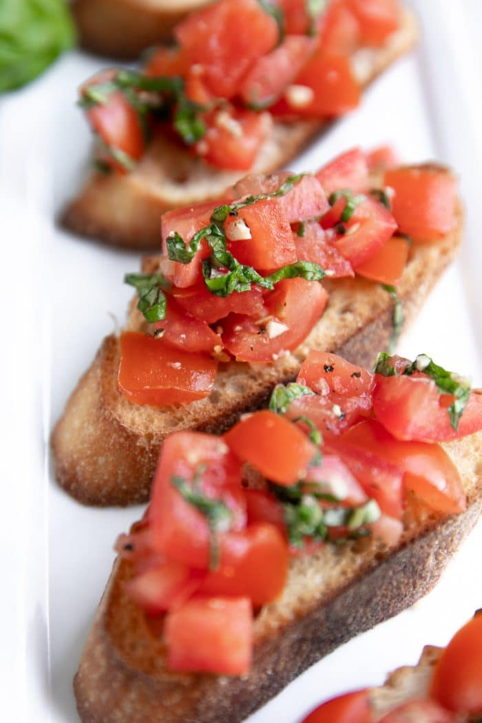 Bruschetta topped with diced Roma tomatoes, minced garlic, olive oil, and fresh basil.