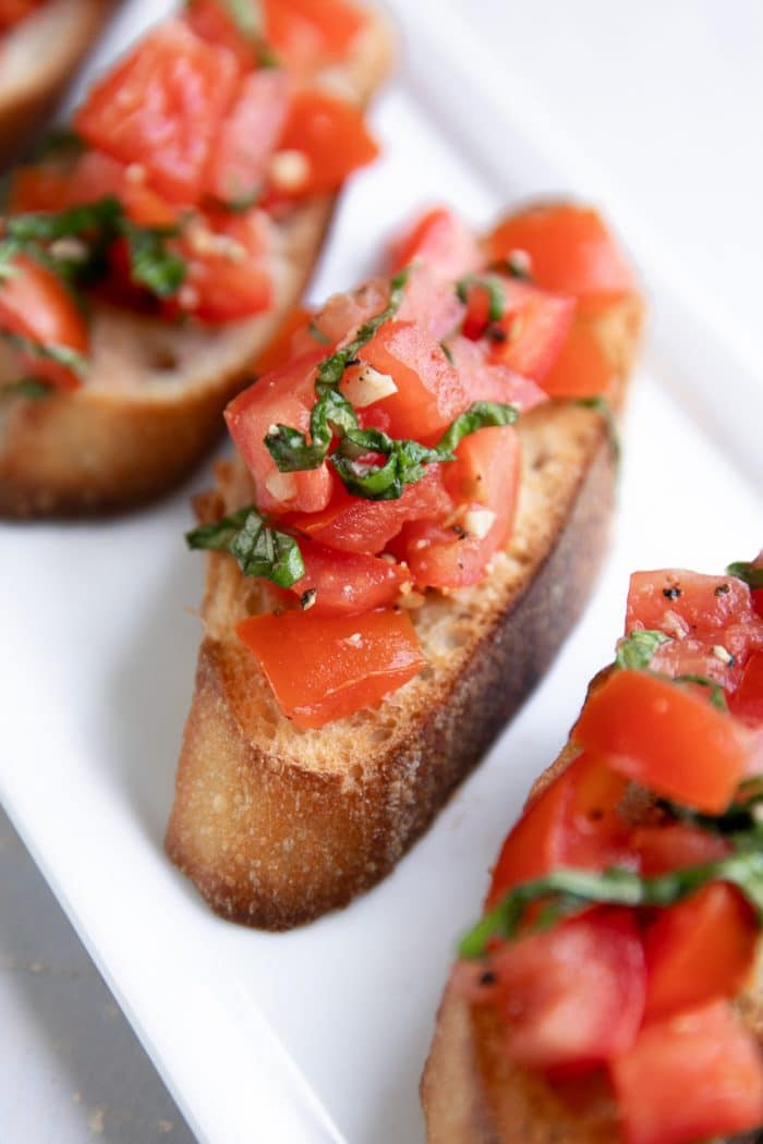 Bruschetta recipe topped with olive oil topped with tomatoes, garlic, and basil.