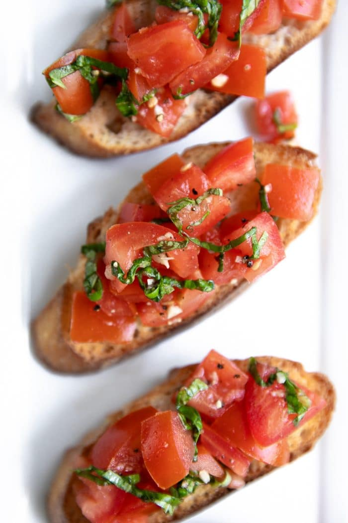 Overhead image of grilled bread with olive oil topped with tomatoes, garlic, and basil.