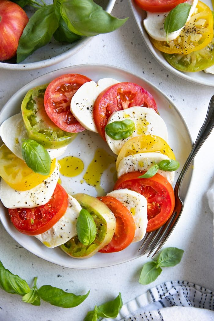 White Salad plate filled a caprese salad made of overlapping slices of fresh tomatoes and mozzarella cheese drizzled with olive oil and garnished with fresh basil.