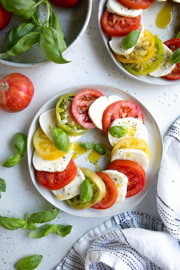 Plate filled with overlapping slices of fresh tomatoes and mozzarella cheese drizzled with olive oil and garnished with fresh basil.