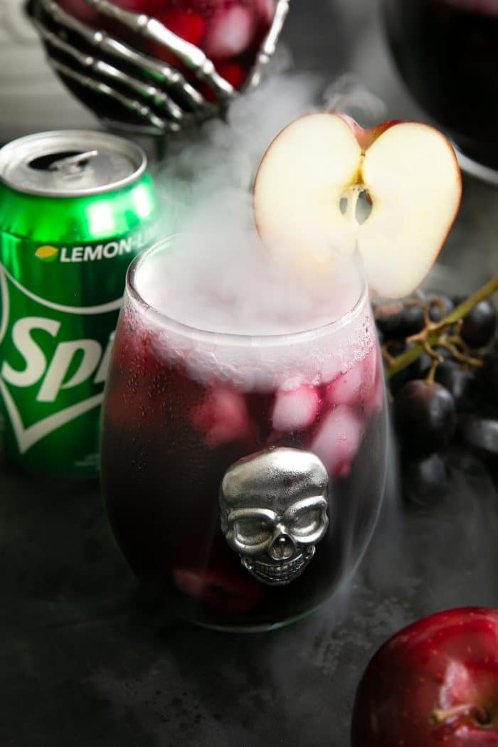 Bubbling and smoking glass of red sangria garnished with a sliced apple.