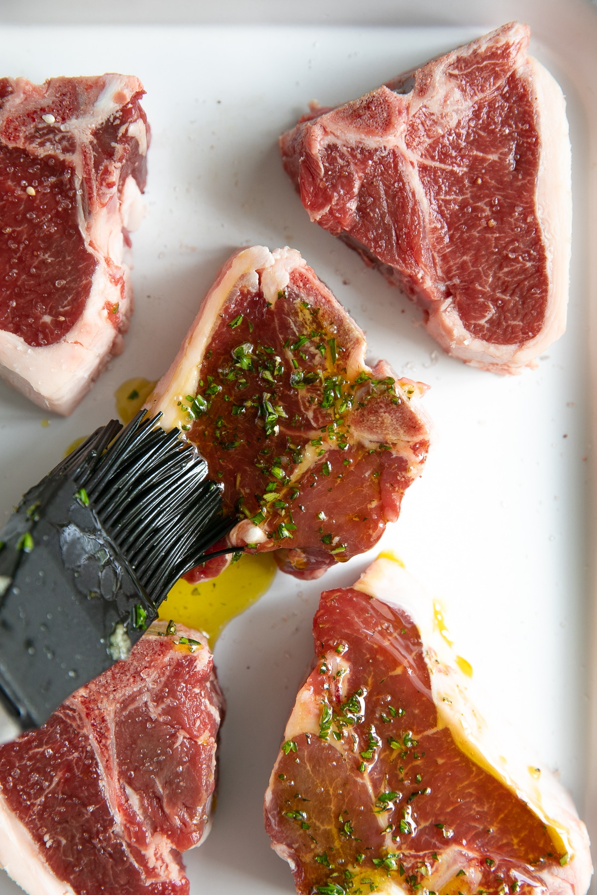 Pastry brush coating raw lamb chops with garlic and herb marinade.