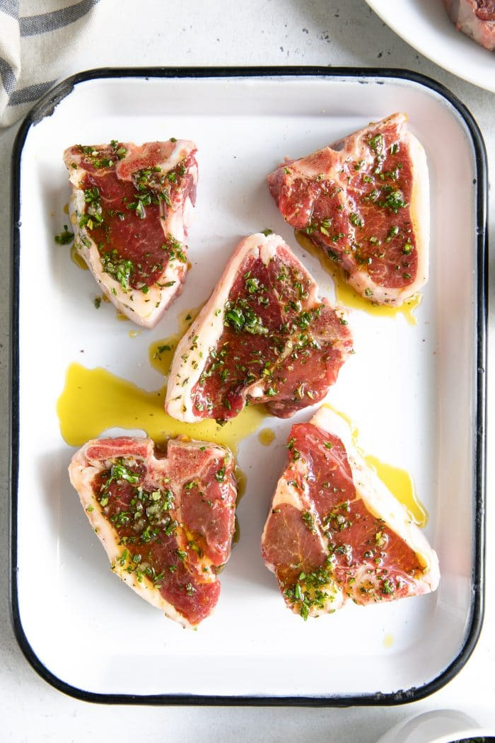 Five lamb chops on a white baking sheet marinating in a mixture of olive oil, garlic, and herbs.