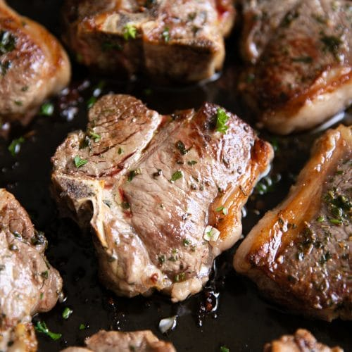 Garlic herb lamb chops in a large skillet.