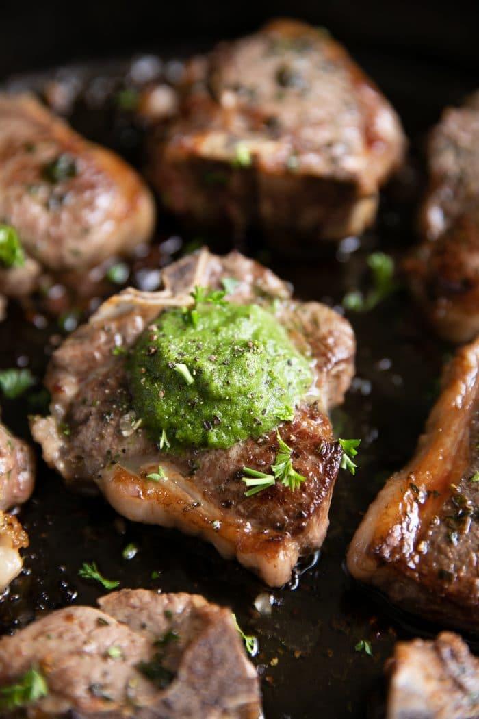Lamb chop in a black skillet fully cooked and topped with a scoop of homemade mint chutney.